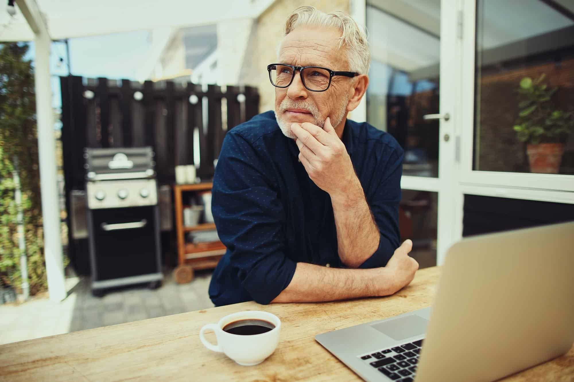 Senior man deep in thought with a laptop and coffee